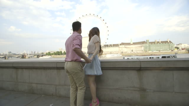 Young couple enjoying and pointing at big wheel