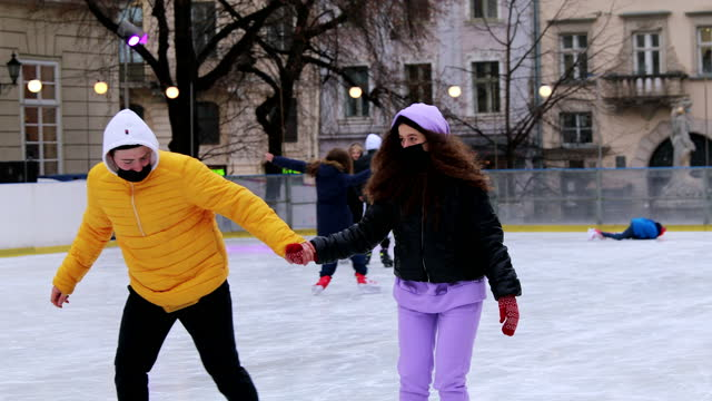 young couple enjoying christmas holidays ice-skating outdoors in the city - ice skating stock videos & royalty-free footage