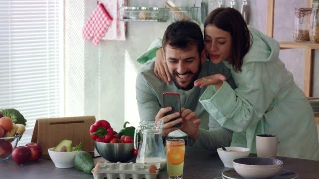 vídeos y material grabado en eventos de stock de pareja joven disfrutando del café por la mañana y teniendo una videollamada - pareja joven