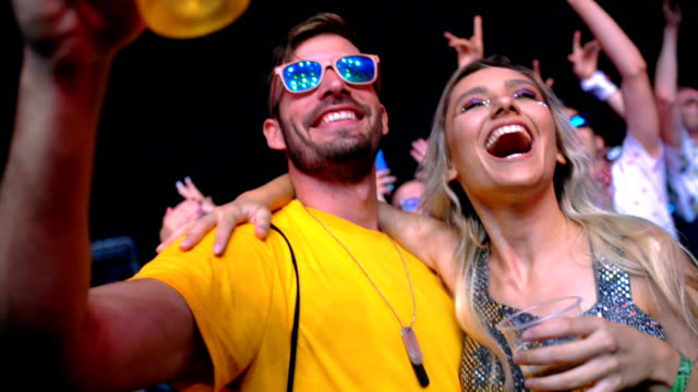 young couple enjoying concert, slow motion. - blonde hair stock videos & royalty-free footage