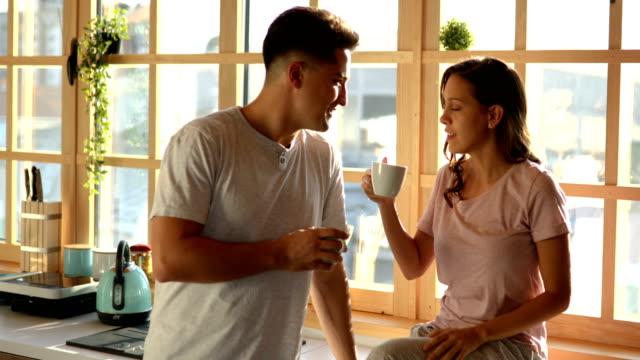 vídeos de stock, filmes e b-roll de pares novos que apreciam o café da manhã na cozinha antes do trabalho - casal jovem