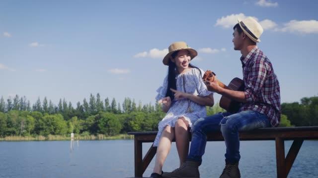 vídeos de stock, filmes e b-roll de casal jovem desfrutando tocando guitarra e sentado à beira do lago e o céu azul no fundo, cópia espaço - casal jovem