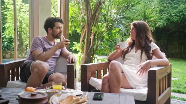 vídeos y material grabado en eventos de stock de pareja joven disfrutando de la mañana de fin de semana relajado en home deck - mesa muebles