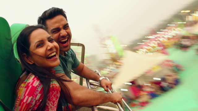 Young couple enjoying rides, Suraj Kund Fair, Faridabad, Haryana, India