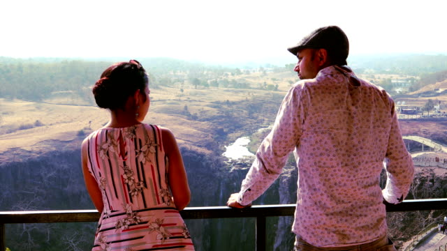 young couple enjoying scenic view of patalpani waterfall from house balcony - married stock videos & royalty-free footage