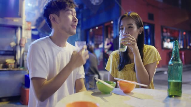 ストリートフードを楽しむ若いカップル - 飲み物点の映像素材/bロール