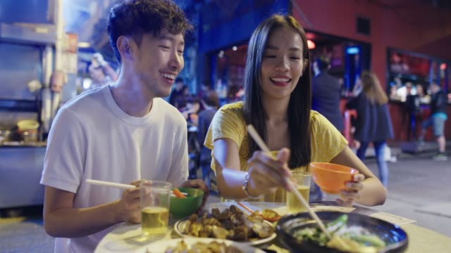 young couple enjoying street food - chinese ethnicity stock videos & royalty-free footage