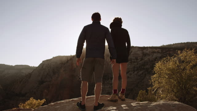 4k uhd: young couple enjoying the sunrise from cliffs edge - zion national park stock videos & royalty-free footage