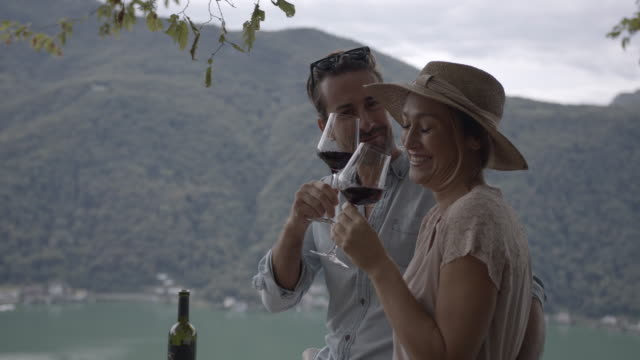 young couple enjoying the view and sharing wine - discovery stock videos & royalty-free footage