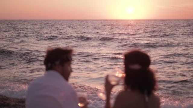 junges paar genießt wein am strand - weinglas stock-videos und b-roll-filmmaterial
