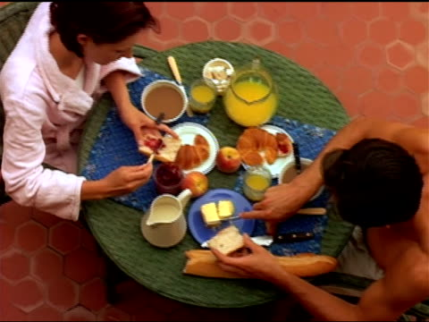 A young couple enjoys a breakfast an outdoor table.