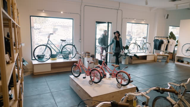 a young couple enter a small bicycle store and shop - window display stock videos & royalty-free footage