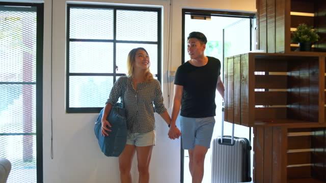 荷物を持ってホームに入る若いカップル - 建物入口点の映像素材/bロール