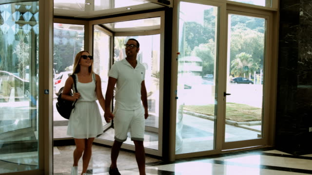 young couple entering to the hotel - lobby stock videos & royalty-free footage