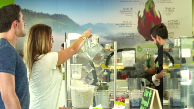 MS young couple enters juice bar and looks at menu to decide which juice to order while employees behind the counter prepare juices and smoothies