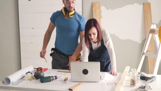 vidéos et rushes de jeunes couples examinant des plans tout en étant sur le chantier de construction dans leur appartement - classe ouvrière