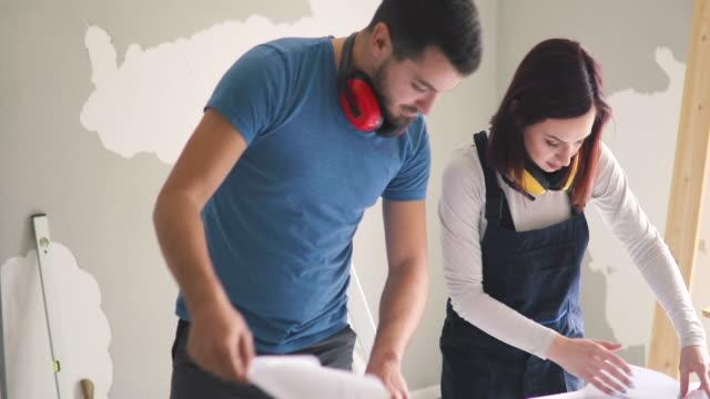 vídeos y material grabado en eventos de stock de joven pareja examinando los planos mientras está en el sitio de construcción en su apartamentojoven pareja examinando los planos mientras está en el sitio de construcción en su apartamento - reforma