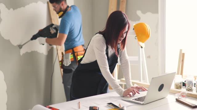 vídeos y material grabado en eventos de stock de una pareja joven examinando planos mientras está en la obra en su apartamento - reforma