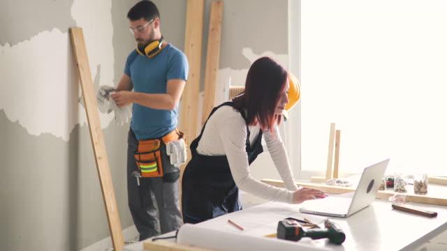 vídeos de stock e filmes b-roll de young couple examining blueprints while being on construction site in their apartment - bricolage