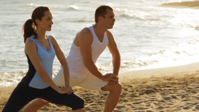 vídeos y material grabado en eventos de stock de young couple exercising on the beach - encuadre de tres cuartos