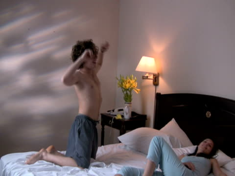 young couple exhaustion: man drops on bed next to woman - pillow stock videos and b-roll footage