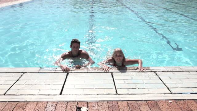 young couple exiting swimming pool - piscina pubblica all'aperto video stock e b–roll