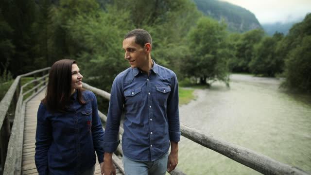 vídeos de stock, filmes e b-roll de pares novos que expressam seu amor na natureza - jeans