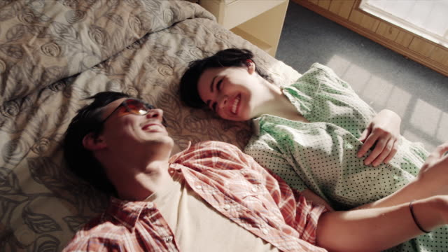 young couple fall onto motel bed laughing - mattress stock videos and b-roll footage