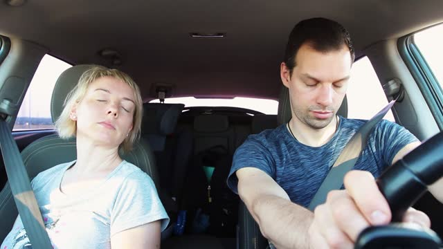 a young couple falls asleep while driving a car during a road trip. a tired driver husband closes eyes and exhausted drowsy man holds the steering wheel while wife sleeps - passenger seat stock videos & royalty-free footage