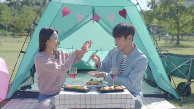 stockvideo's en b-roll-footage met young couple feeding each other sushi in front of a tent in the han river park - koreaanse etniciteit