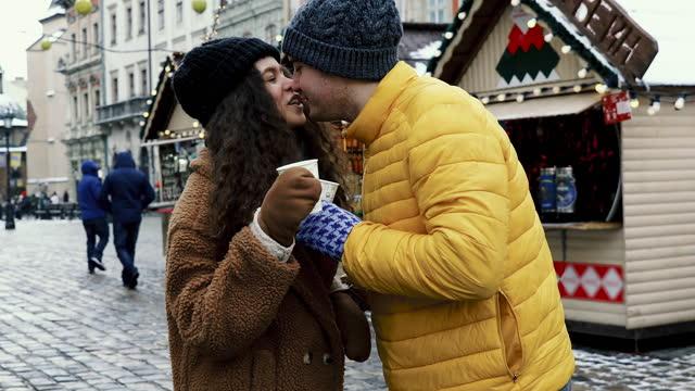 stockvideo's en b-roll-footage met jong paar dat liefde en geluk bij de markt van de stad van kerstmis voelt - warme dranken