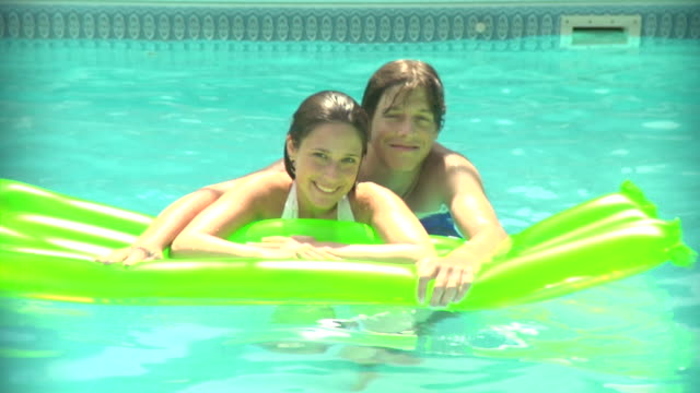 stockvideo's en b-roll-footage met cu, young couple floating on air mattress in swimming pool, portrait, middlesex, new jersey, usa - 2007