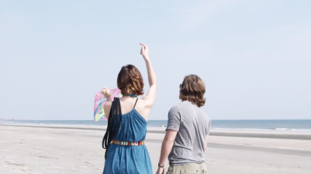 ms slo mo young couple flying kite at beach / isle of palms, south carolina, usa - carolina beach stock videos and b-roll footage