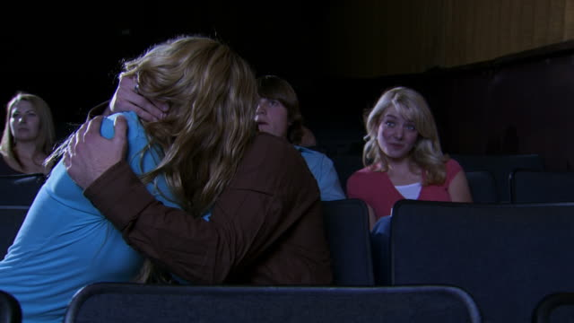 vidéos et rushes de young couple french kissing at movie theater - couple d'adolescents