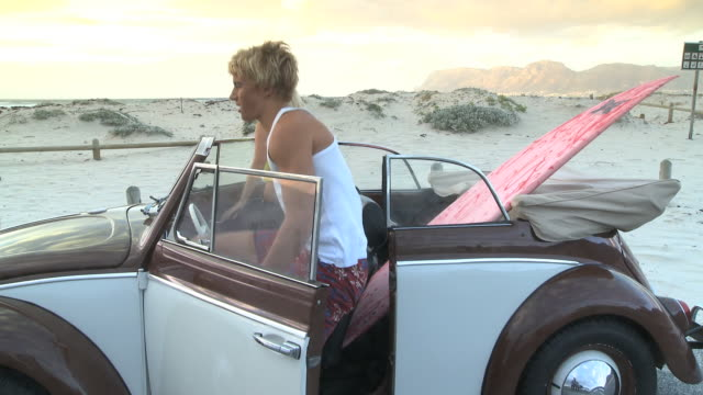 Young couple getting out car and picking up surfboard, Cape Town, South Africa