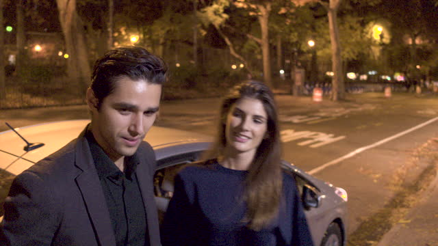 vidéos et rushes de young couple getting out of back seat of car, night - débarquement