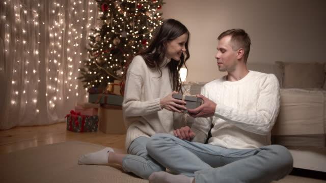 una giovane coppia si fa regali a natale. - inside of video stock e b–roll