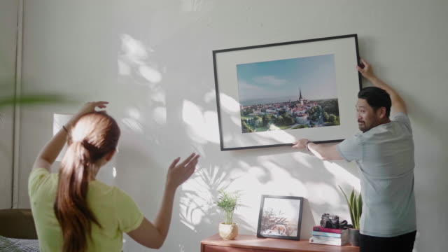 young couple hanging a picture frame on the living room wall - picture frame stock videos & royalty-free footage