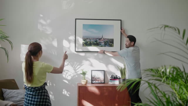 young couple hanging a picture frame on the living room wall - hanging stock videos & royalty-free footage