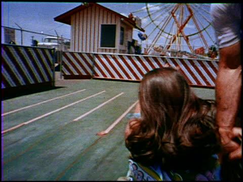 vidéos et rushes de a young couple has fun at an amusement park circa 1969 the couple runs toward a ferris wheel rides a slide rides on a merry go round rides a small... - parc d'attractions