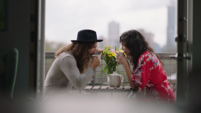 young couple have a morning cup of tea on balcony overlooking downtown austin, texas. - balcony stock videos & royalty-free footage