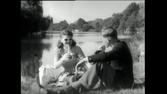 young couple have a picnic beside a lake; 1955 - old stock videos & royalty-free footage