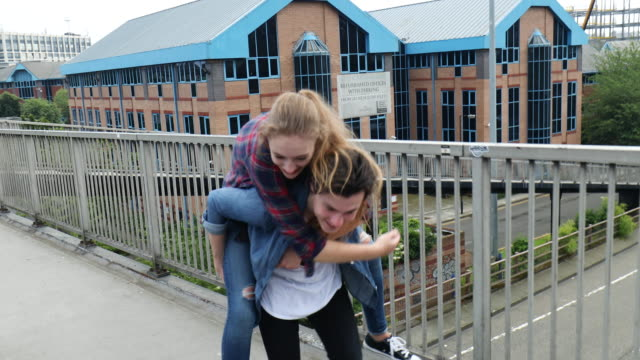 young couple have a piggy back ride on a bridge - attività del fine settimana video stock e b–roll