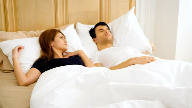 Young couple have problem with man's snoring in bed at home, people, family and bedtime concept