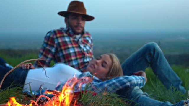 vídeos de stock, filmes e b-roll de jovem casal tendo uma fogueira à noite na natureza - reclinando