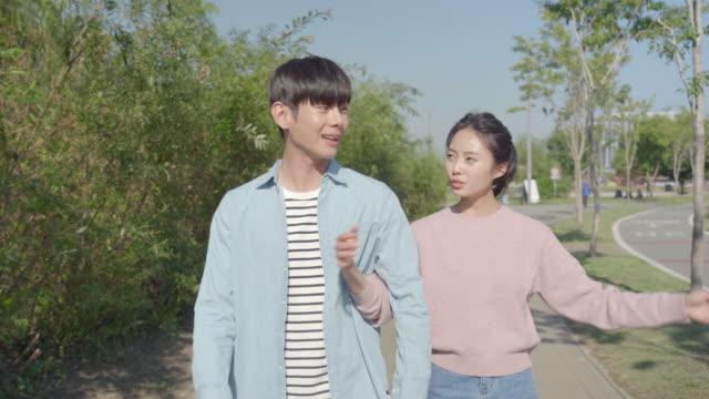 vídeos de stock, filmes e b-roll de young couple having a conversation while strolling in the han river park - de braços dados