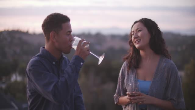 vídeos de stock, filmes e b-roll de young couple having a drink together outdoors - boyfriend