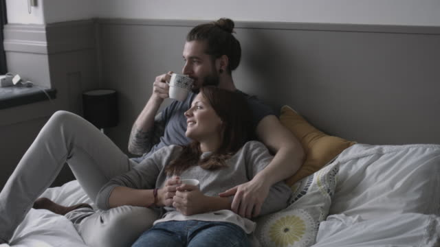 young couple having coffee in bed - mug stock videos and b-roll footage