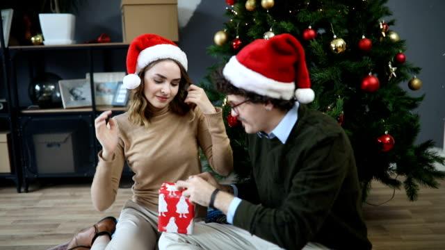 young couple having fun celebrating christmas with gifts - dorso umano video stock e b–roll