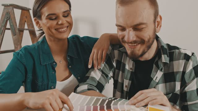 young couple having fun deciding on a color for their wall paint - color swatch stock videos & royalty-free footage